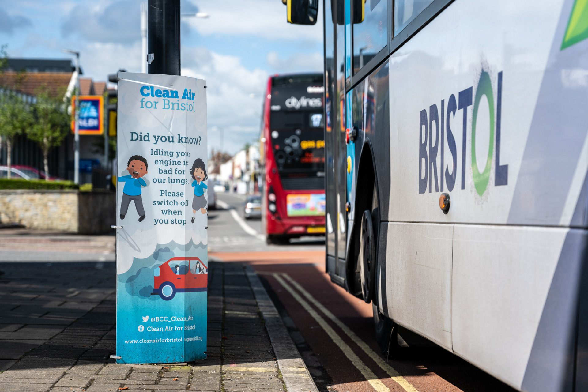 """Buses on the Fishponds Road pass a city council """"Clean Air For Bristol"""" poster asking motorists to switch off their engines when stationary."""